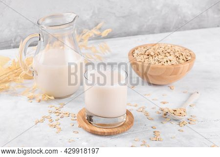Vegan Non Dairy Alternative Milk. Oat Milk In A Jug On A Grey Stone Table Background And A Bowl With