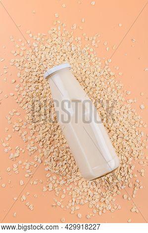 Vegan Non Dairy Alternative Milk. Oat Milk In A Bottle On The Oat Flake On Pastel Peach Color Backgr
