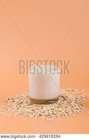 Vegan Non Dairy Alternative Milk. Oat Milk In A Glass On The Oat Flake On Pastel Peach Color Backgro