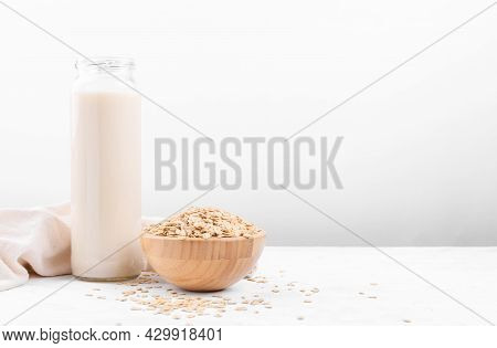 Vegan Non Dairy Alternative Milk. Oat Milk In A Bottle And A Bowl With Oat Flake On Grey Stone Table