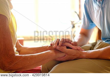 Worried Caucasian Man Gently Stroking Hand Of His Sick Old Mother Showing Care Or Love. Son Comforti