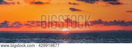 Panorama Of Sundown Over Sea Horizon At Sunset. Natural Sunrise Sky Warm Colors Over Ocean.