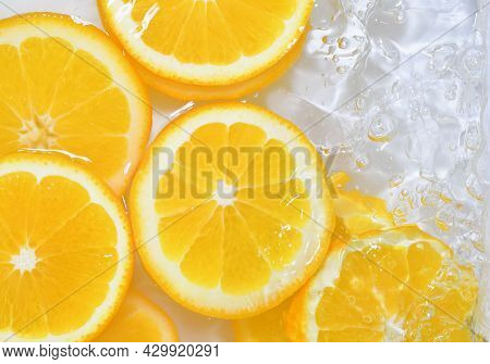 Slices Of Oranges In Water On White Background. Oranges Close-up In Liquid With Bubbles. Slices Of J