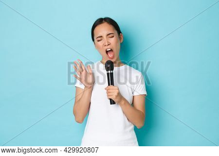 Lifestyle, People And Leisure Concept. Carefree Beautiful Asian Girl Singing Sing In Microphone With
