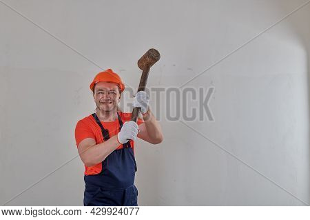 Cheerful Man With A Sledgehammer In His Hands In A Helmet