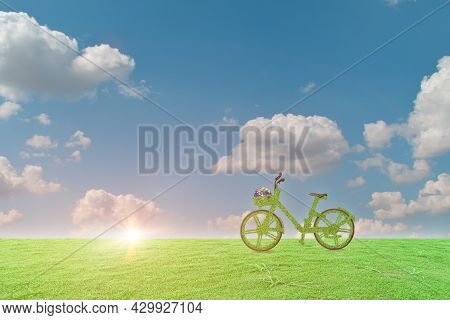 Green Ecological Bicycle With Globe On Grass Field And Blue Sky Background. Environment And Earth Da