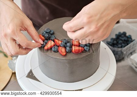Woman Pastry Chef Decorates Grey Cake With Berries, Close-up. Cake Making Process, Selective Focus