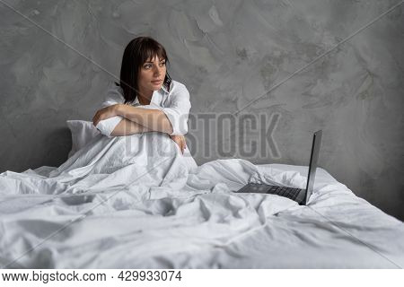 Pretty Girl In The Morning In The Bedroom With A Laptop Looks Out The Window Works Remotely As A Fre