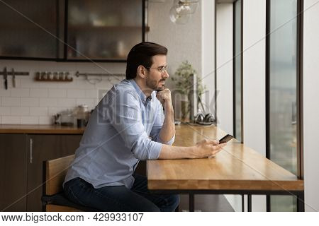 Peaceful Businessman Sit In Office Kitchen Hold Smartphone Daydreaming