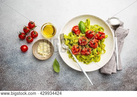 Green Tagliatelle Pasta With Cherry Tomatoes And Basil On Gray Background, Top View