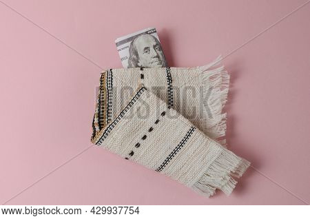 Money And White Fringed Napkin On Pink Background. The One Hundred Dollar Bill Is Hidden In The Fold