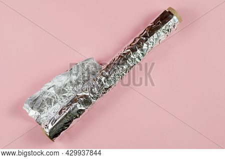 Crumpled Foil Opposite The Pink Background. Roll Of Aluminum Foil For Food Packaging With An Uneven