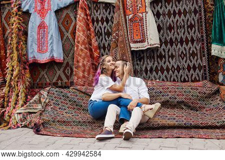 Couple In Love Buys A Carpet And Handmade Textiles At An Oriental Market In Turkey. Hugs And Cheerfu
