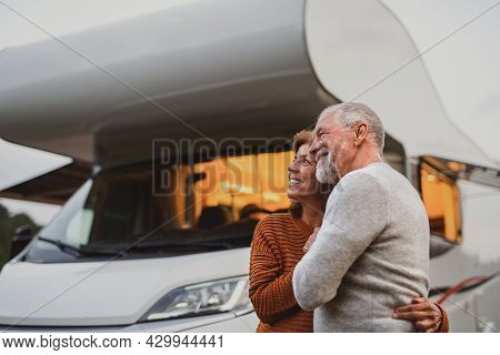 Senior Couple Standing And Hugging Outdoors At Dusk, Caravan Holiday Trip.