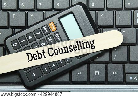 Laptop Keyboard, Calculator, Ice Cream Stick With The Word Debt Counseling