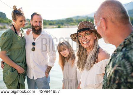 Happy Multigeneration Family On Summer Holiday, Walking By Lake.