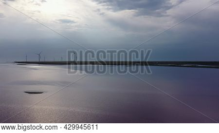 A Wind Farm On The Shores Of A Pink Lake. Evening Time. Aerial View. Lake Lemuria (pink Lake) Is A L