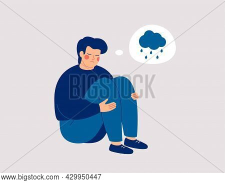 Unhappy Man Hugs His Knees And Sits On The Floor With Rainy Cloud Above His. Sad Boy Is Crying.  Mal