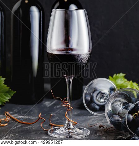 Wine Glass With Red Wine. Wine Composition On Black Stone Table Square. Red Wine Bottles, Grape Bunc