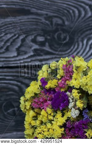 Statice Bouquet Of Flowers Of Different Colors. Against The Background Of Pine Boards. Close-up Shot