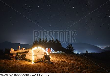 Young Man Resting Near Lighted Tent Outdoors At Night. Group Of Tourists Relaxing On Meadow Under Ev