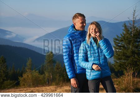 Couple Of Hikers Sincerely Laughing While Resting In The Mountains. Cheerful Vacation In Nature On B