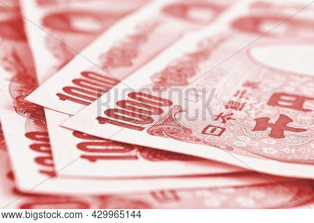 Close-up Of Several Japanese 1,000 Yen Notes. Light Red Tinted Backdrop Or Background About Money, B