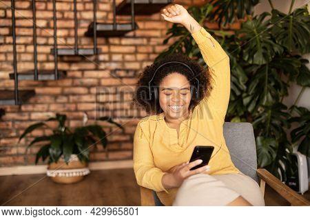Young African-american Woman In Headphones Listening Listening Energetic Music, Enjoys Favorite Trac