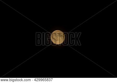 Full Yellow Moon On A Pure Black Sky. Full Moon Phase, Craters Visible. Moscow, Russia. Close-up.