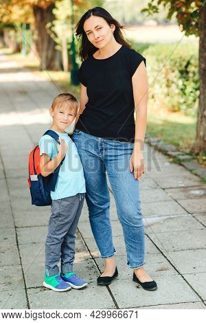 Little Student With School Bag Hugs Mother Near School. Back To School Concept. Happy Schoolboy With