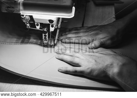 Working Process Of Leather Craftsman. Tanner Sews Leather On A Special Sewing Machine, Close Up. Wor