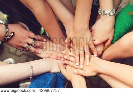 Sign Of Trustful Friendship. Top View Group Of Children Stacking Hands Outdoors. Concept Of Friendsh