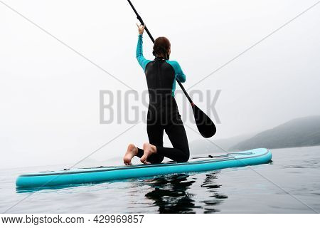 Back View Active Sportswoman In Diving Suit Floating On Stand Up Paddle At Fog Sea Scenery