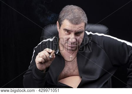 A Charming White Man Smokes A Cigar In A Chair And Looks At The Camera With A Smile From Under His B