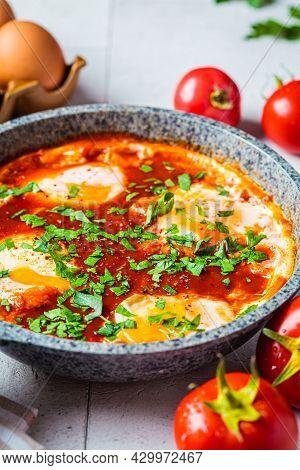 Traditional Israeli Shakshuka In A Gray Frying Pan. Fried Eggs In Tomato Sauce.