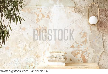 Stack Of Neatly Folded Clothes Lies On Raw Wooden Shelf Against Beige Color Grunge Concrete Unfinish