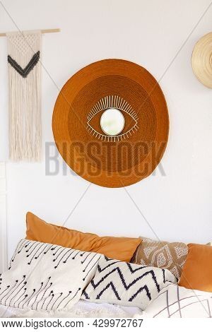 Patterned And Colorful Pillows On Comfy Bed In Boho Style Bedroom With Straw Round Carpet On White W