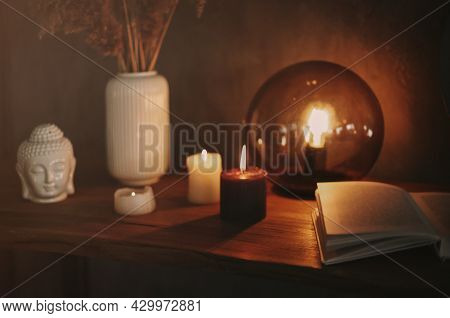 Round Mirror On Wooden Shelf With Two Burning Candles And Small Porcelain Buddha Head Reflected In C