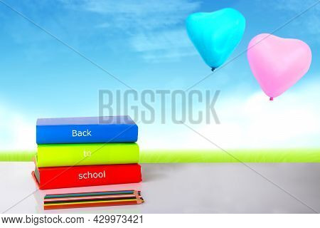 Closeup Of Colourful School Supplies On The Table In Front Of An Abstract Summer Background With Two