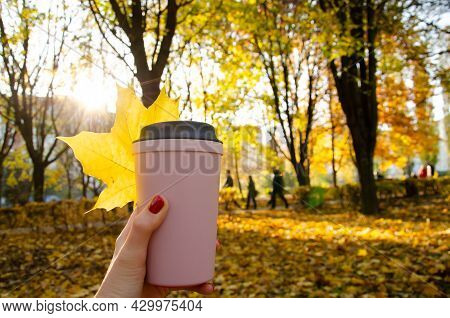 Caucasian Woman Holding Cup Of Coffee With Yellow Maple Leaf On The Background Of Autumn Landscape A