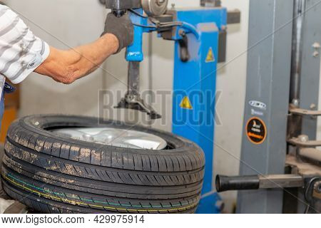 Mechanic Changing Tire In Car Service. Tire Rotation Machine.car Mechanic Mounts Tire On Wheel In A