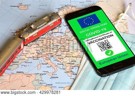 The Digital Green Pass Of The European Union On Smartphone With A Model Train And Surgcal Masks Over