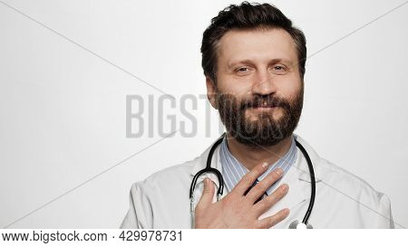 Doctor Respect Bow. Smiling Man Doctor On White Background Looking At Camera And Puts His Hand On Ch