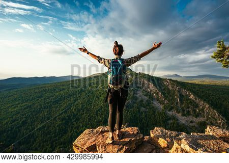 A Woman With A Backpack Stands On The Top Of A Mountain With Her Hands Raised And Admires The Beauty