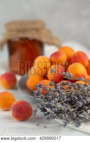 Blurred Image Of Apricot, Lavender Sprigs And Apricot Jam In Glassware. Apricot And Lavender Jam.