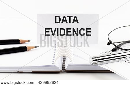 Text Data Evidence On Paper Card,pen, Pencils, Glasses,financial Documentation On The Table - Busine