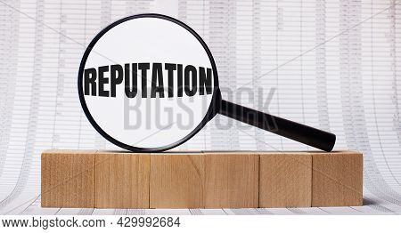 Against The Background Of Reports On Wooden Cubes - A Magnifying Glass With The Text Reputation. Bus