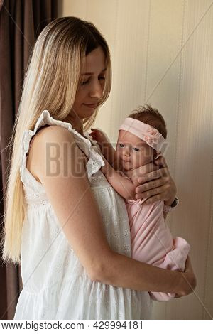 Portrait Of Young Caucasian Mother Holds Hug Little Newborn Baby Two Weeks Old At Home. Happy Mom Em