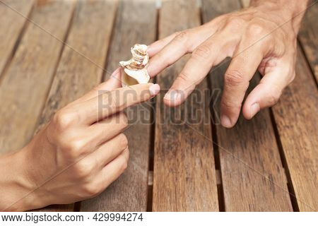 Midsection couple Exchanging seashel Wedding Ring against wooden background