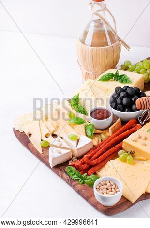 Cheese Platter With Assorted Cheese, Sausage, Jam, Black Olives, Pine Nuts And Grapes. Appetizer Var